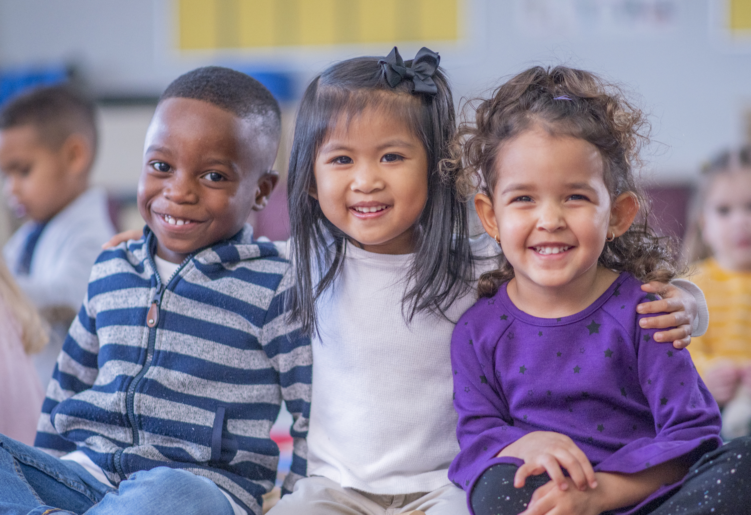 A multi-ethnic group of children sit close together on the floor, with their legs crossed and their arms around one another. They are smiling and enjoying their time together.
