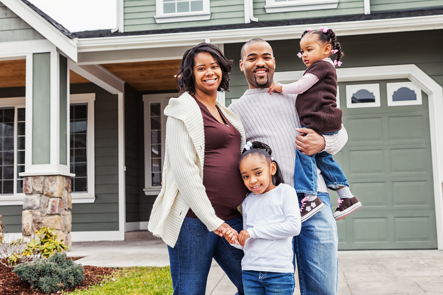 Portrait of a young African American family of four in front of their house.